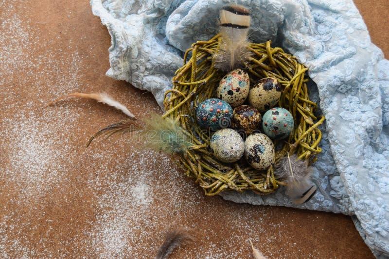 Fond lumineux de Pâques ; Fleurs de panier et de brin d'oeufs de pâques sur le fond bleu de table photos libres de droits