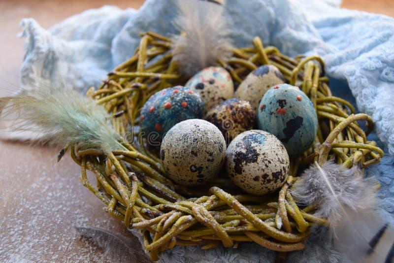 Fond lumineux de Pâques ; Fleurs de panier et de brin d'oeufs de pâques sur le fond bleu de table images stock