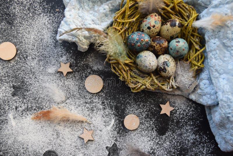 Fond lumineux de Pâques ; Fleurs de panier et de brin d'oeufs de pâques sur le fond bleu de table photographie stock