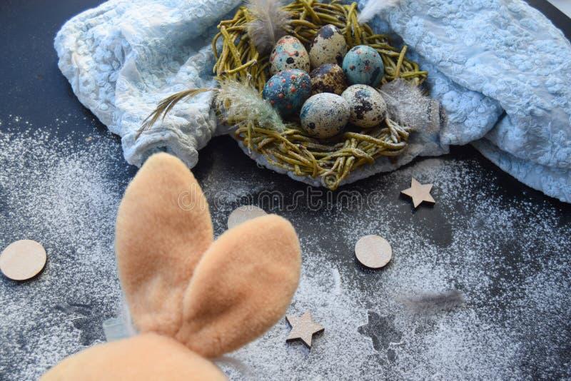 Fond lumineux de Pâques ; Fleurs de panier et de brin d'oeufs de pâques sur le fond bleu de table images libres de droits