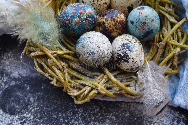 Fond lumineux de Pâques ; Fleurs de panier et de brin d'oeufs de pâques sur le fond bleu de table image libre de droits