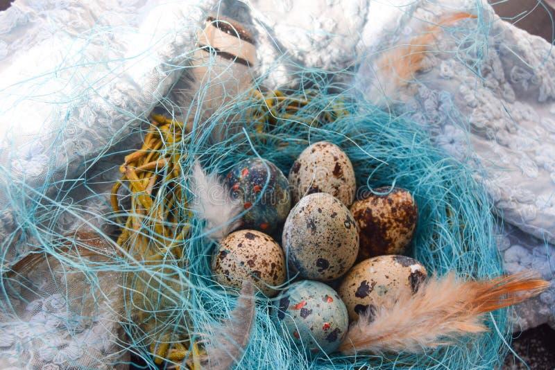 Fond lumineux de Pâques ; Fleurs de panier et de brin d'oeufs de pâques sur le fond bleu de table photo libre de droits