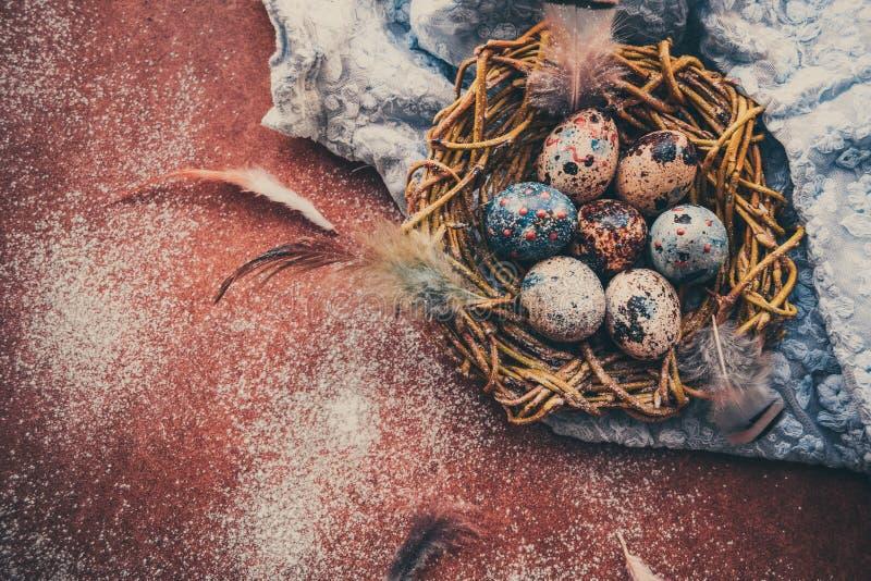 Fond lumineux de Pâques ; Fleurs de panier et de brin d'oeufs de pâques sur le fond bleu de table image stock