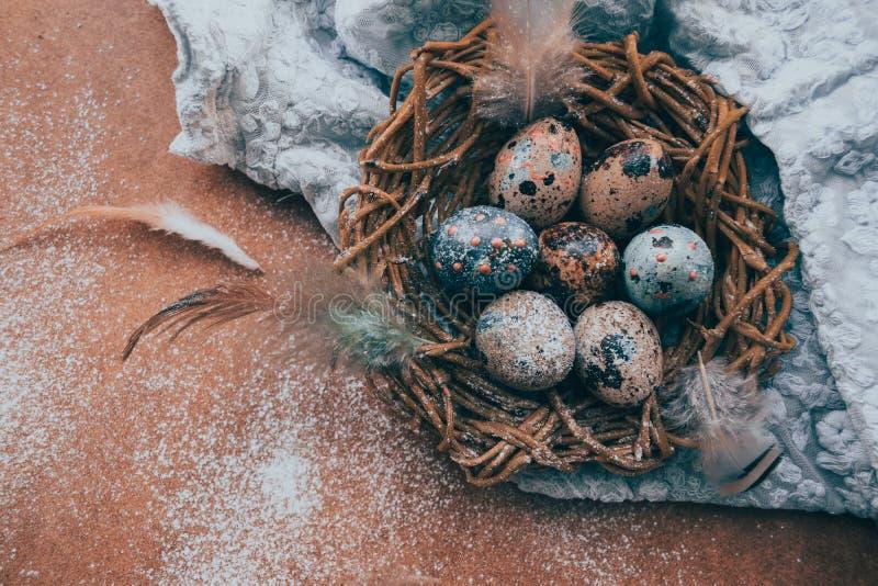 Fond lumineux de Pâques ; Fleurs de panier et de brin d'oeufs de pâques sur le fond bleu de table photo stock