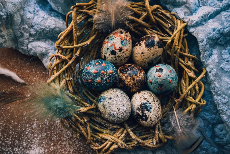 Fond lumineux de Pâques ; Fleurs de panier et de brin d'oeufs de pâques sur le fond bleu de table photos stock