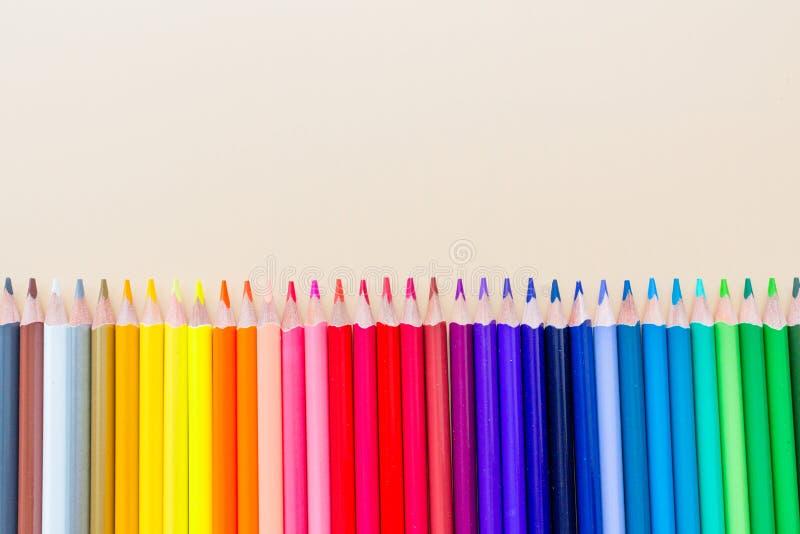Fond lumineux et coloré avec beaucoup de crayons se trouvant sur le papier orange en pastel Vue supérieure, configuration plate,  images stock