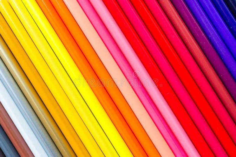 Fond lumineux et coloré avec beaucoup de crayons se trouvant sur le papier orange en pastel Vue supérieure, configuration plate,  photographie stock libre de droits