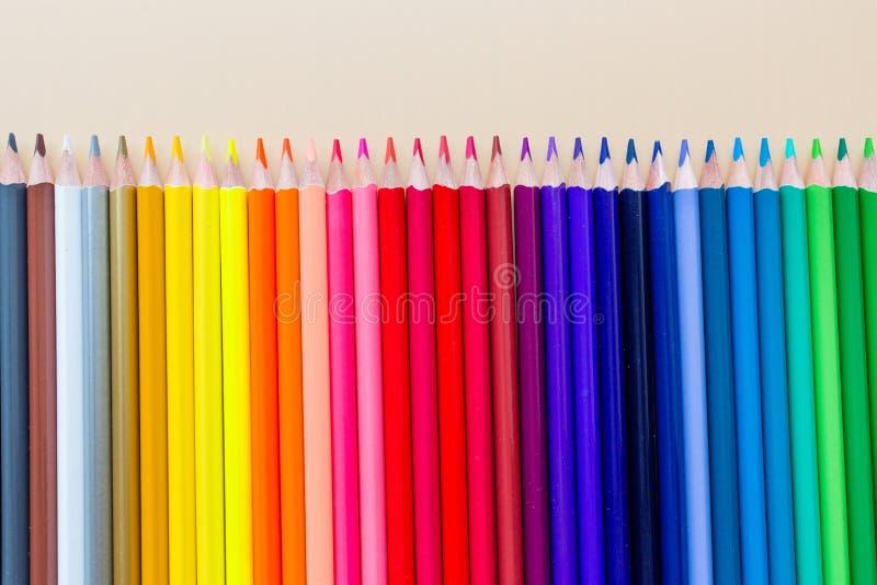 Fond lumineux et coloré avec beaucoup de crayons se trouvant sur le papier orange en pastel Vue supérieure, configuration plate,  photos libres de droits