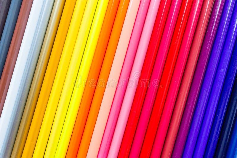 Fond lumineux et coloré avec beaucoup de crayons se trouvant sur le papier orange en pastel Vue supérieure, configuration plate,  photos stock