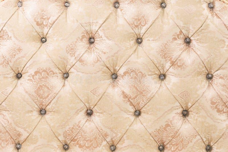 Fond mou beige de modèle de tapisserie avec les boutons symétriques sur les coins des diamants Meubles mous et chers photos stock