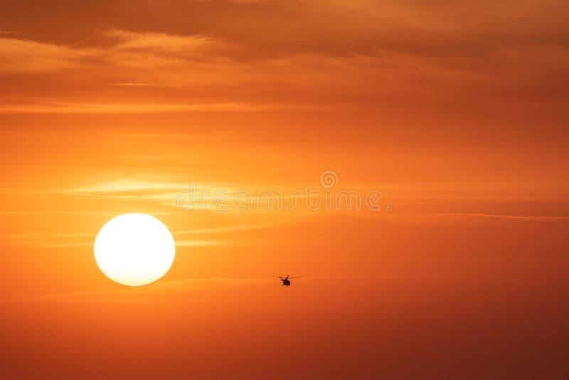 Fond orange de ciel de coucher du soleil ? la soir?e avec les nuages et la silhouette de l'h?licopt?re image libre de droits