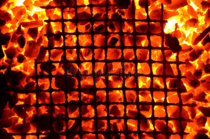 Fond orange lumineux d'anthracite brûlant de charbon et d'un trellis étendu photos stock