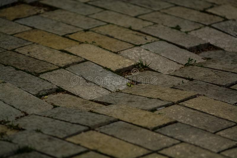 Fond ou texture d'une tuile cassée et égale avec des corrections de lumière et de baisses Blocs en pierre sur le trottoir photographie stock libre de droits