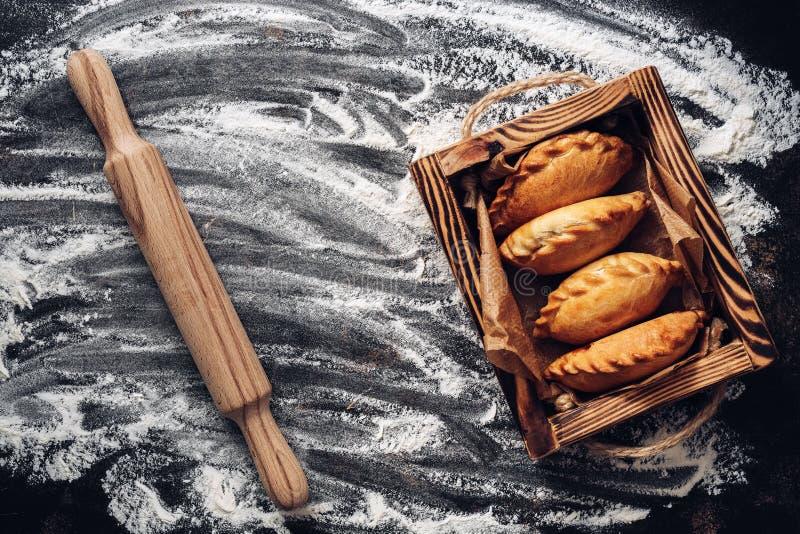 Fond, pâtisserie, farine et goupille de cuisson Tartes russes dans un plateau en bois Vue sup?rieure, l'espace de copie photographie stock