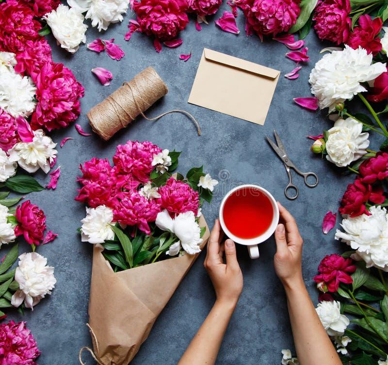 Fond plat de fleur d'été de configuration Un bouquet des fleurs des pivoines, les mains des femmes et conservent une tasse de thé images stock