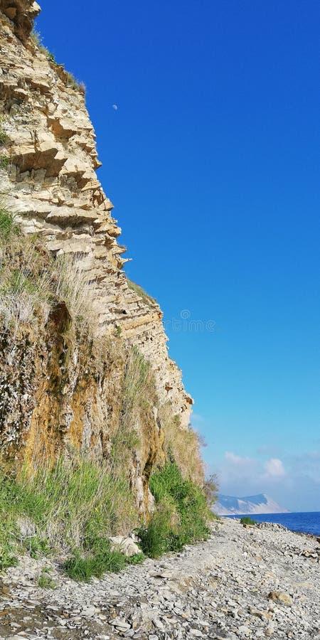 Fond positif lumineux paysage de montagne contre le ciel sans nuages bleu et la mer photo stock