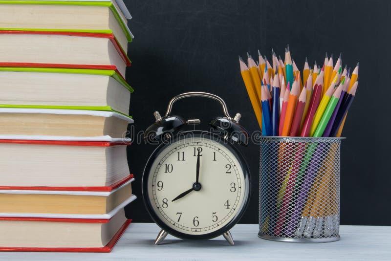 Fond pour l'étude, avec une pile de livres, de période et d'un verre de crayons multicolores photographie stock