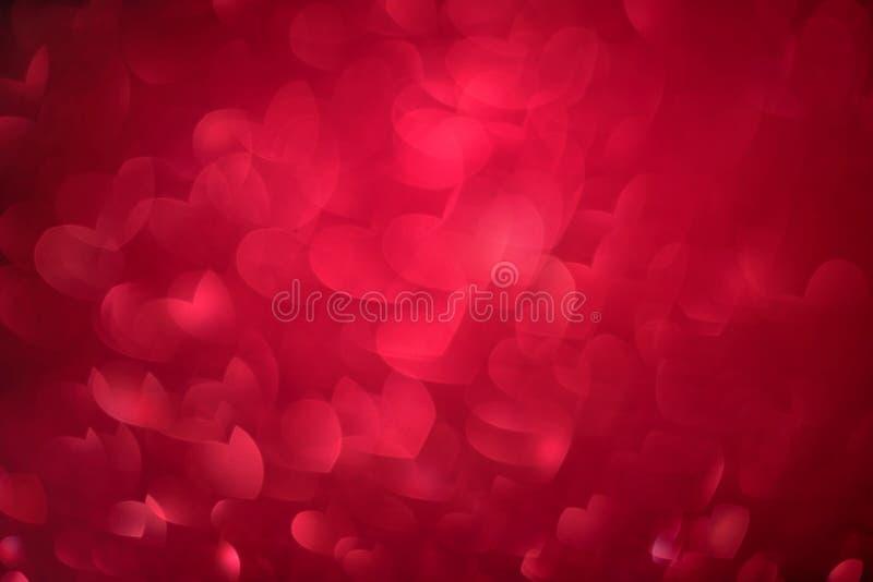 Fond rouge de coeurs de bokeh avec les lumières lumineuses de scintillement pour le jour de Saint-Valentin ou de femmes Texture D images libres de droits