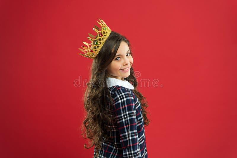 Fond rouge de couronne d'usage de fille Concept corrompu d'enfant Princesse égocentrique Monde me tournant autour L'enfant porten photographie stock