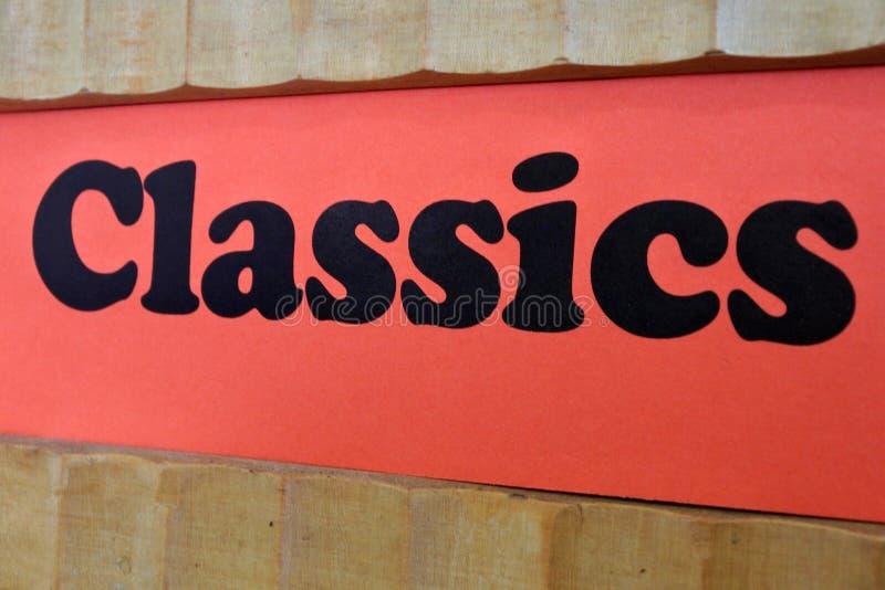 Fond rouge de signe de classiques sur des étagères à livres images libres de droits