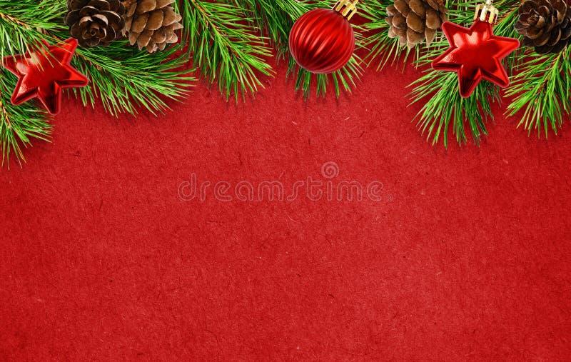 Fond rouge de vacances avec des brindilles d'arbre de Noël, cônes, boules photo stock