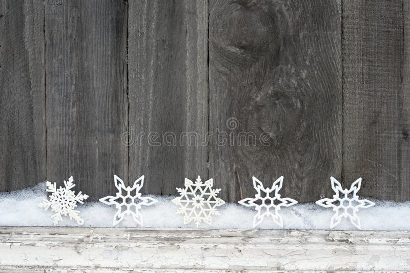 Fond rustique d'hiver avec des flocons de neige de scintillement et neige sur la texture en bois Fond de carte de voeux de Noël e photos stock