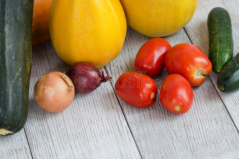 Fond sain de nourriture Différents légumes frais sur un Tableau blanc en bois Tomates, courgette, aubergine, oignon angle images libres de droits