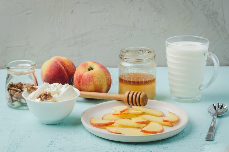 Fond sain de petit d?jeuner Pêche, miel, fromage de lait et blanc et noix sur une table bleue photographie stock