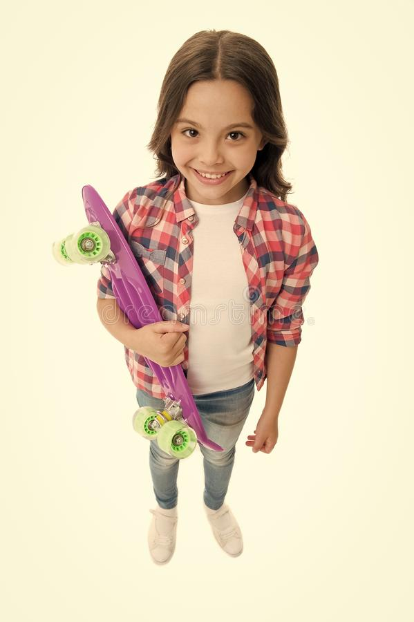 Fond of skateboarding. Kid girl happy carries penny board. Child likes skateboarding with penny board. Modern teen hobby. How to ride skateboard. Girl happy royalty free stock photos