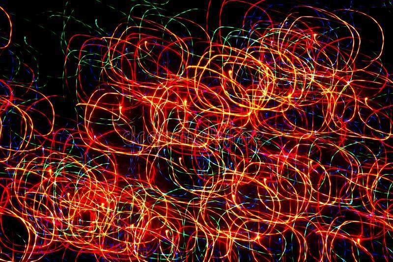 Fond, texture, modèle abstrait lumineux dans différentes lignes d'une couleur, rayures et taches sur un fond noir, cercles, néon photos libres de droits