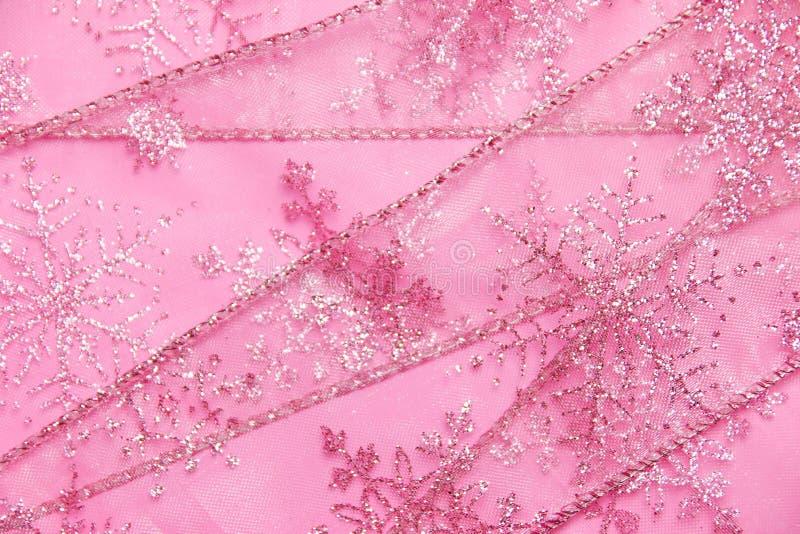 Fond texturisé abstrait de ruban net rose avec des flocons de neige de scintillement photographie stock