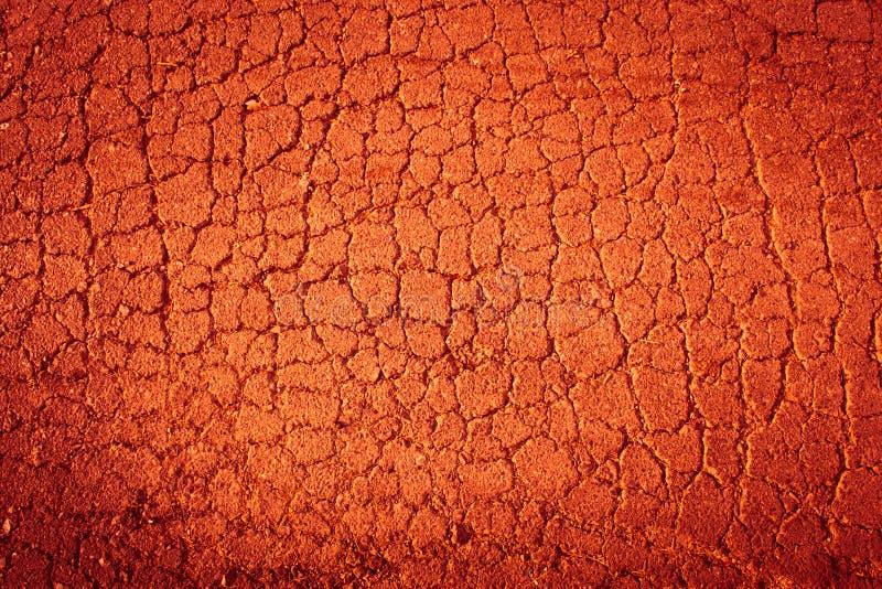 Fond texturisé de la terre criquée d'un rouge ardent image libre de droits