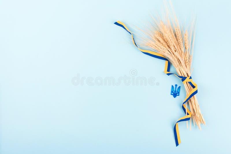 Fond ukrainien avec des symboles nationaux, manteau du ruban de trident de bras, jaune et bleu, épillets d'or de blé sur le bleu  photos stock