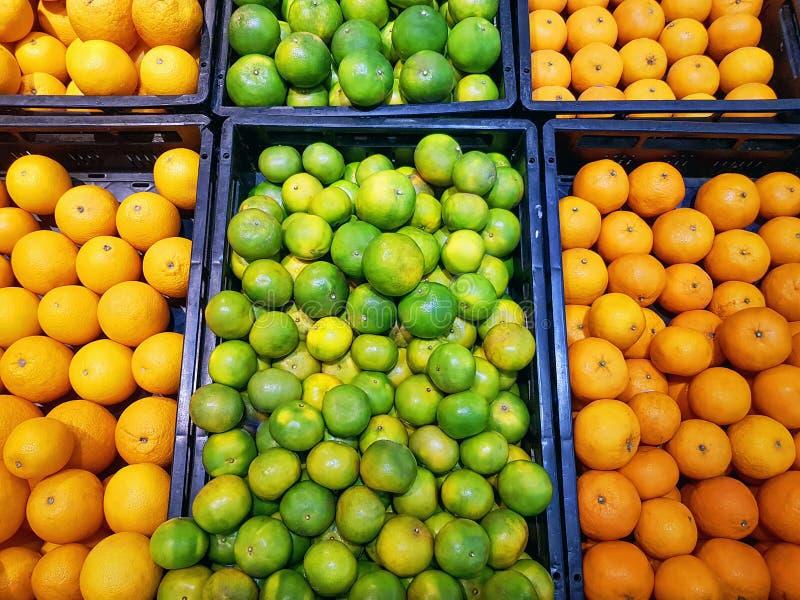 Fond vibrant des piles des fruits oranges frais dans des plateaux photos libres de droits