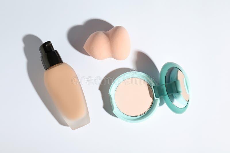 Fondamento della pelle, polvere e spugna di trucco sulla vista bianca e superiore fotografia stock libera da diritti