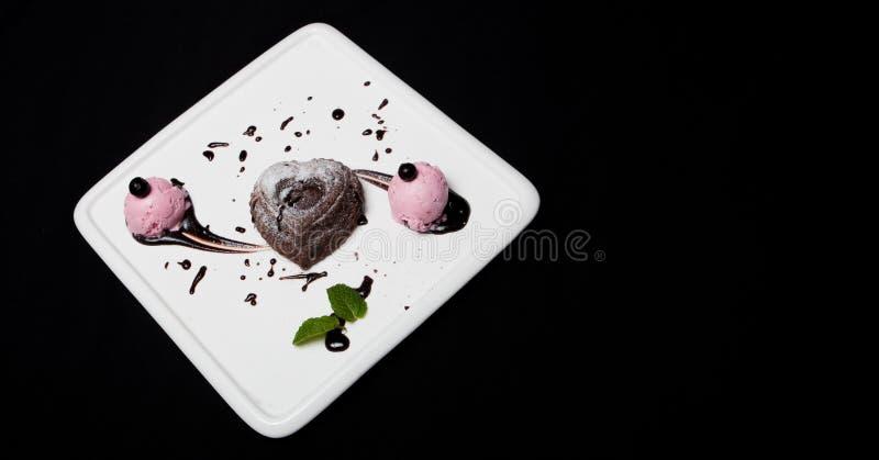 Fondan σοκολάτα επιδορπίων με το παγωτό σε ένα άσπρο πιάτο σε ένα μαύρο υπόβαθρο Έξοχο γαλλικό επιδόρπιο σοκολάτας fondan, θέση φ στοκ φωτογραφίες με δικαίωμα ελεύθερης χρήσης
