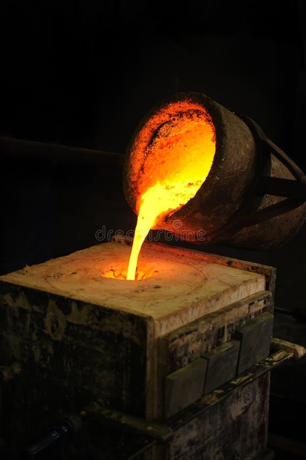 Fonderia - il metallo fuso ha versato dalla siviera in moul immagini stock