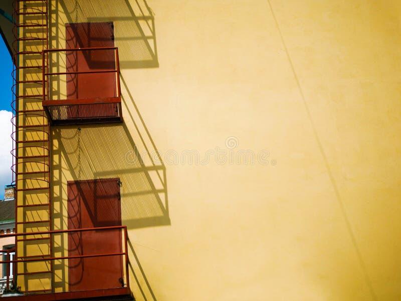 Fondo abstracto interesante con la sombra del balcón en la pared amarilla fotografía de archivo
