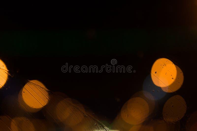 Fondo abstracto oscuro con el bokeh anaranjado y amarillo brillante con las gotas de agua en la calle en la noche a través del vi foto de archivo