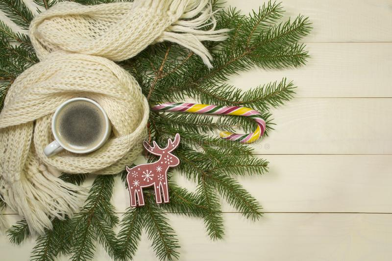 Fondo accogliente di Natale con lo spazio della copia Albero di Natale, sciarpa bianca, caffè caldo, giocattolo dei cervi e lecca fotografia stock