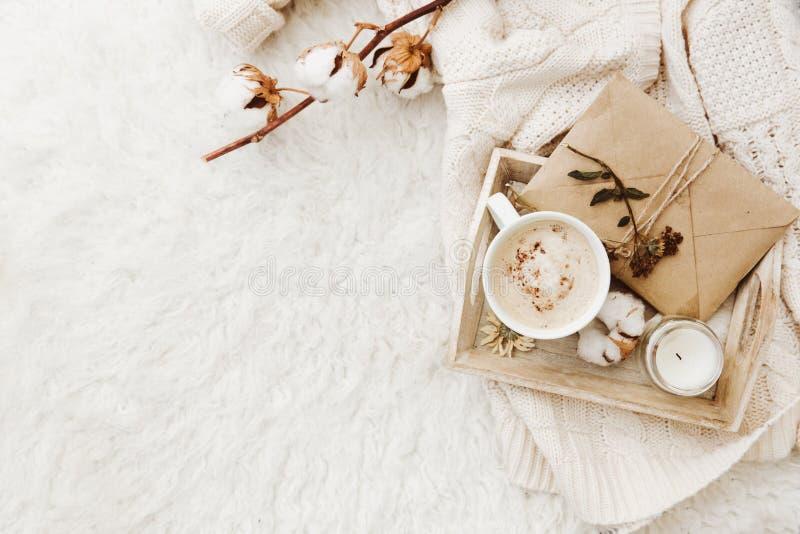 Fondo acogedor del invierno con la taza de café, de suéter caliente y de viejas letras imagenes de archivo