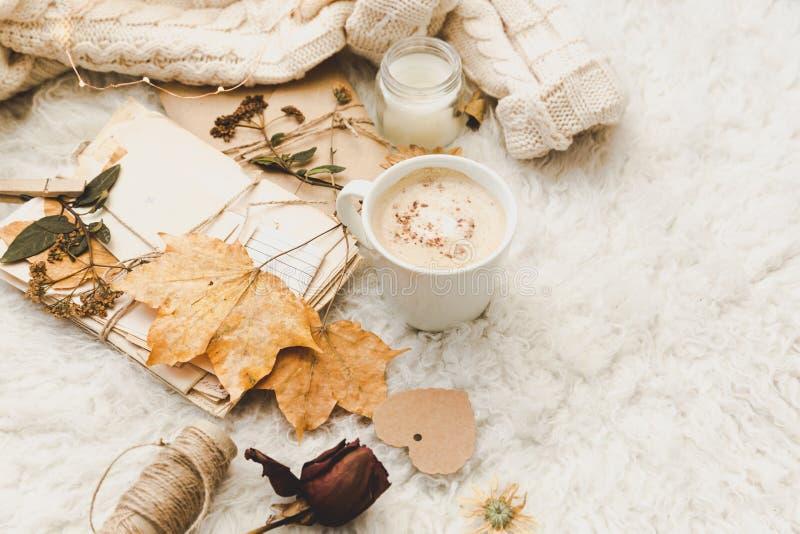 Fondo acogedor del invierno con la taza de café, de suéter caliente y de viejas letras Endecha plana fotos de archivo libres de regalías