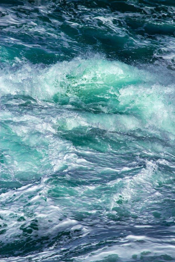 Fondo acuático de las ondas de la resaca del mar que salpican cerca para arriba con agua verde azul clara y la espuma blanca fotografía de archivo libre de regalías