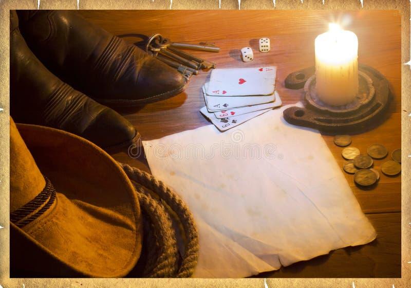 Fondo ad ovest americano con le carte della mazza ed i vestiti del cowboy immagine stock libera da diritti