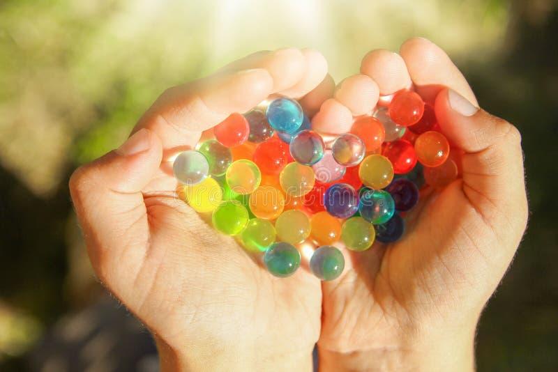 Fondo agradable de diversas bolas de los colores en manos imagenes de archivo