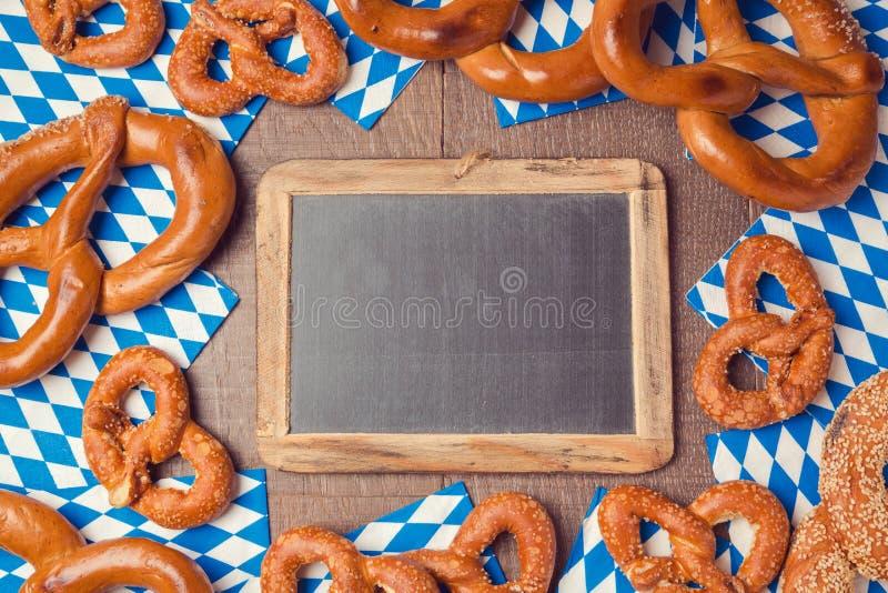 Fondo alemán del festival de la cerveza de Oktoberfest con la pizarra y el pretzel imagenes de archivo
