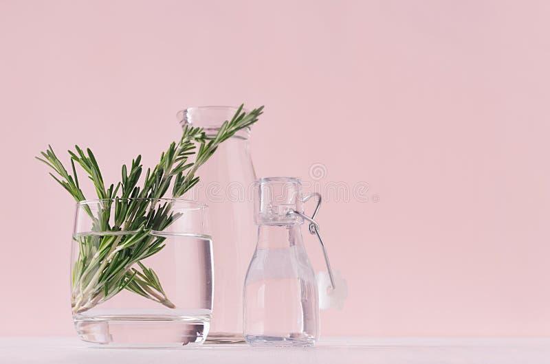 Fondo apacible de la vainilla de la primavera del romero fresco del ramo en las botellas de cristal y retras en la tabla blanca y foto de archivo libre de regalías
