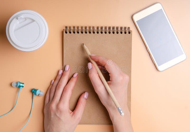 Fondo arancio variopinto con le mani che scrivono in taccuino vuoto, cuffie della donna dello smartphone della tazza di caffè fotografie stock