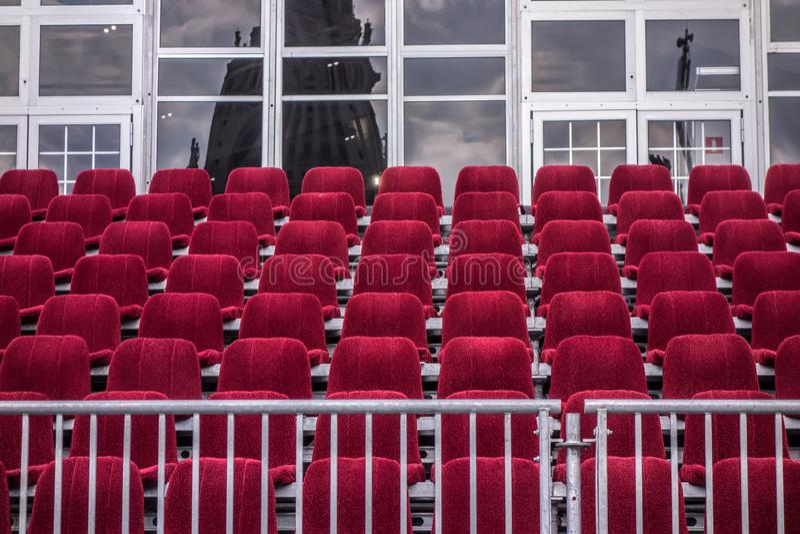 Fondo architettonico, paesaggio urbano Le sedie rosse sono allineate nelle file immagine stock libera da diritti