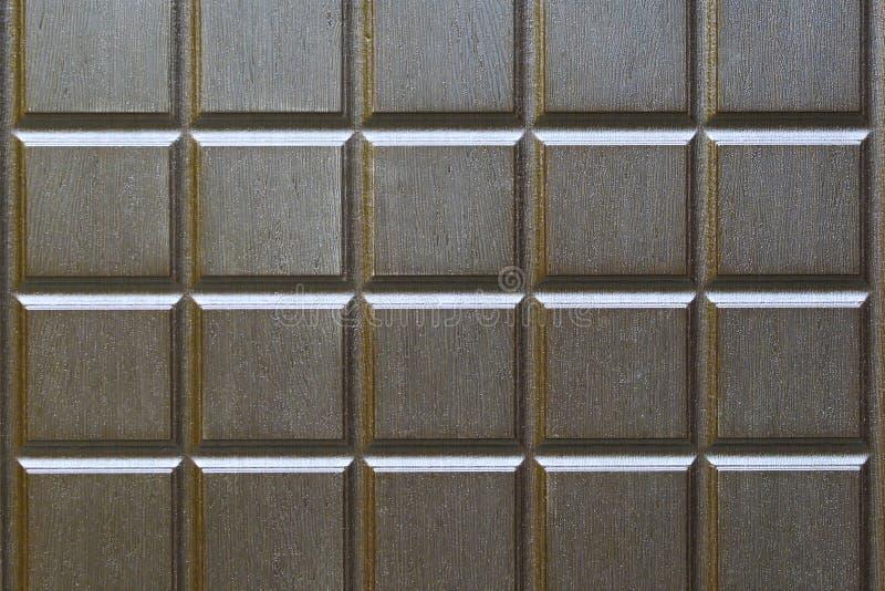 Fondo astratto dai quadrati di colore marrone Frammento di un metallo, entrata principale con imitazione di legno immagini stock